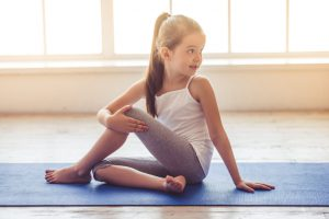 Charming little girl is smiling while doing yoga in fitness hall